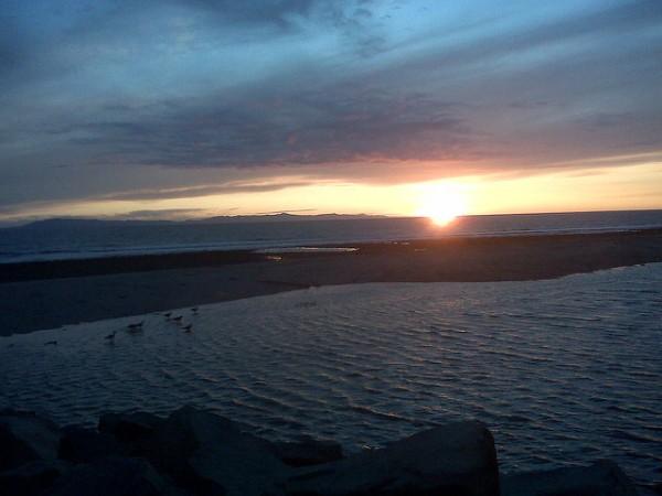 A sunset over the ocean with a dark sky