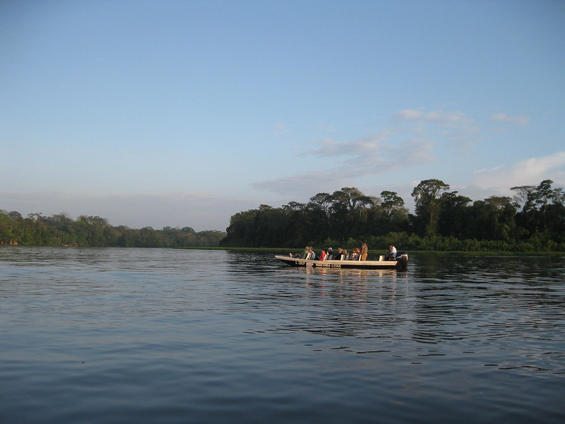 A flat boat on a river in Costa Rica in early morning. There are about 10 people on the boat.